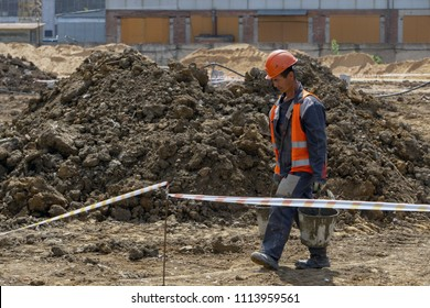 Khimki, Russia - June 13, 2018: The worker at the construction site is carrying a bucket
