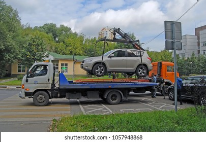 KHIMKI, RUSSIA  - SEPTEMBER, 2017: Two tow trucks take a car parked in violation of traffic rules