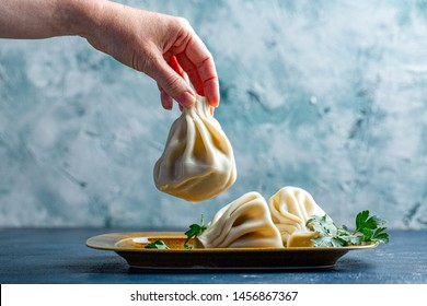 Khinkali, Georgian dumplings, traditional Georgian cuisine. Cook's hand puts khinkali on a plate on the side. Blue background, copy space.