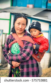 Khinmey Gompa and Ugyenling Temple, Arunachal Pradesh - circa February 2012: Woman with black hair carries her young son on her back in Khinmey Gompa, Arunachal Pradesh. Documentary editorial.