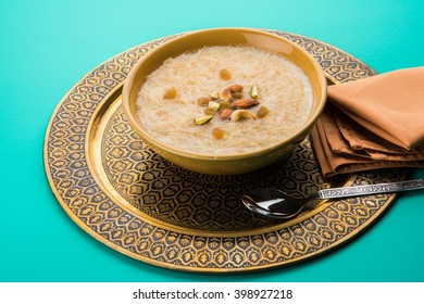 Khir or kheer payasam also known as Sheer Khurma Seviyan consumed especially on Eid or any other festival in india/asia. Served in a bowl dry fruits over colourful/wooden background. Selective focus