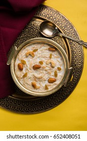 Khir or kheer payasam also known as Sheer Khurma Seviyan consumed especially on Eid or any other festival in india/asia. Served with dry fruits toppings in a bowl over colourful/wooden background.