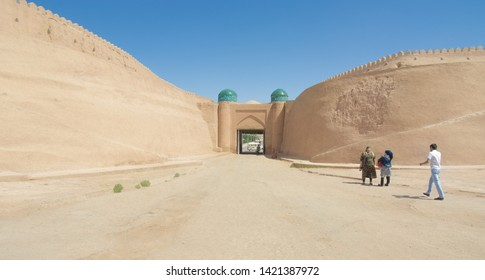 Khiva, Uzbekistan–May 2, 2019: Uzbek women in national clothes are talking to each other at the gates of the old city of Khiva (Uzbekistan), framed by a city wall. Behind the gate opens a modern city.