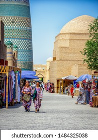 Khiva, Uzbekistan - 06/14/2019 - Two local women of different races in traditional dress shopping in the street market