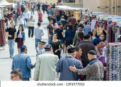 Khiva, Uzbekistan - April, 2019: Local people and tourist on the street of Itchan Kala (old or inner city). Focus on the girl in centre.