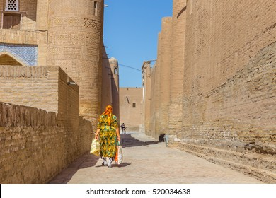 KHIVA, UZBEKISTAN - AUGUST 25, 2016: unidentified woman walks in the fortress Ichon-Qala, the old town of Khiva, in Uzbekistan.