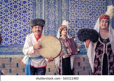 Khiva, Uzbekistan - circa July 2011: People in beautiful folk costumes play music instruments and dance to traditional music in Khiva, Uzbekistan. Documentary editorial.