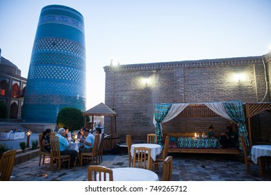 Khiva, Uzbekistan - June 2, 2017: Detail of Kalta Minor minaret in Khiva, Uzbekistan, with some tourists havind dinner.
