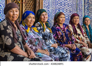 KHIVA, UZBEKISTAN - MAY 23, 2016: Women in colorful, traditional dresses sit and rest in  the courtyard of a mosque in Khiva, Uzbekistan.