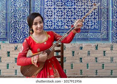 KHIVA, UZBEKISTAN - MAY 24, 2017: Uzbek woman in national costumes play local musical instrument of Dutar, in Khiva, Uzbekistan.