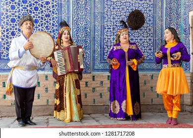 KHIVA, UZBEKISTAN - OCTOBER 10, 2017: Uzbek musicians in traditional clothes play music instruments and sing local songs, in Khiva, Uzbekistan