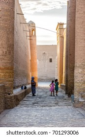 KHIVA, UZBEKISTAN - SEPTEMBER 6: Two kids with older lady in the narrow street in Khiva old town. September 2016