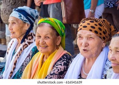 KHIVA, UZBEKISTAN - SEPTEMBER 7: Senior Uzbek women dressed in traditional clothes smiling and showing their golden teeth. September 2016