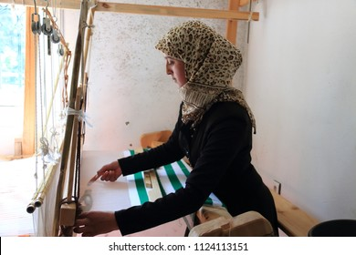 Khizana, Chefchaouen, Morocco - April 29, 2018: a Moroccan woman weaving on an old loom in the rural area of Khizana, Chefchaouen, Morocco