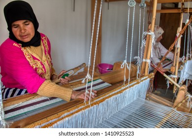Khizana, Chefchaouen, Morocco - May 2, 2019: Moroccan artisan women working traditionally on old looms of a women's cooperative located in the rural area of Khizana, near Chaouen, Morocco