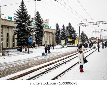 Khmelnytskyi, Ukraine - March 25, 2018: A woman on a snow-covered platform looks out the window of a standing train. Khmelnytskyi