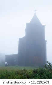 Khmer men walking to the ancient catholic church in the mist of morning, a remote settlement builds by the French colonialists in 1928. Preah Monivong Bokor National Park, Kampot. Public place.