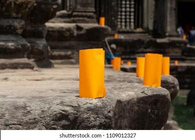 Khmer New Year paper lantern on cambodian temple. Khmer New Year celebration tradition. Paper lantern on Angkor Wat stones. Orange lantern for buddhist ritual. Orange paper light with candle