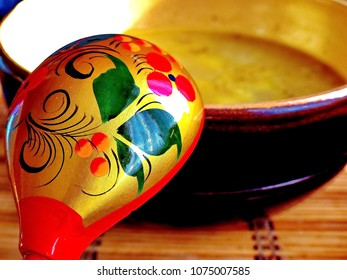 Khokhloma spoon and a bowl of soup. Khokhloma - an ancient Russian folk craft (XVII century). Traditional elements Khokhloma - red juicy berries of mountain ash and wild strawberries