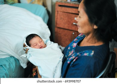 Khon Kaen, Thailand - July 16 : The portrait of baby in hold of mother in Srinagarind Hospital on the July 16, 2017 in Khon Kaen, Thailand.