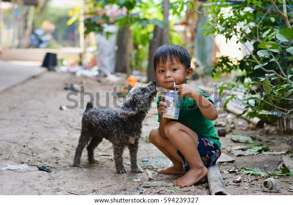 Khon Kaen, Thailand - March 5  2017 : impoverished children and a dog eating milk from donations.