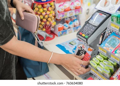 KHONKAEN, THAILAND - NOVEMBER 19, 2017 : Illustrative editorial, Customer make a payment for goods by using seven card or e-money at the counter service of 7-Eleven shop. Cashless society concept.