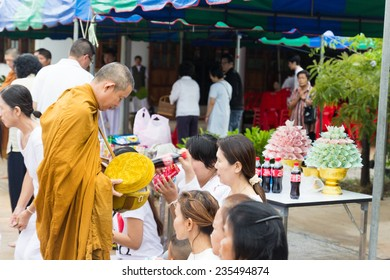 Khonkaen, Thailand - October 26, 2014: People put food offerings in a Buddhist monk's alms bowl for virtue at Wiweksikkaram Forest Monastery in Pon district.