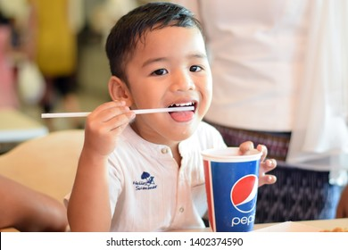 KhonKaen,Thailand - May 19,2019 : The boy is enjoying and drinking Pepsi water at the restaurant happily.