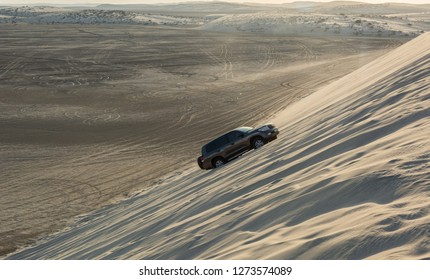 Khor Al Adaid, Qatar - November 5, 2016. 4WD vehicle driving up a sand dune in Khor Al Adaid desert in Qatar.
