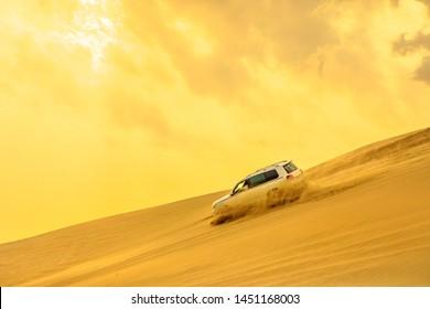Khor al Udaid, Qatar - February 19, 2019: Dune Bashing at sunset sky near Saudi Arabia, Persian Gulf, Middle East. Inland sea is a major tourist destination for Qatar. Discovery and adventure travel.