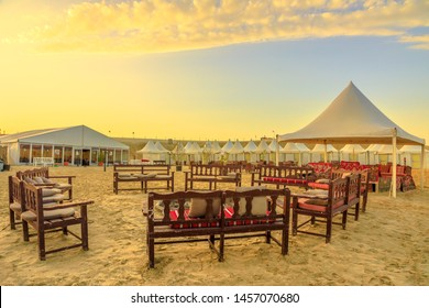Khor al Udaid, Qatar - February 19, 2019: tents at QIA desert camp at Inland Sea in Persian Gulf at sunset sky. Middle East, Arabian Peninsula. Inland sea is a major tourist destination for Qatar.