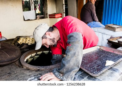 Khorog, Tajikistan, August 20 2018: A man bakes traditional street food Samsa or Samsy in a wood-burning oven