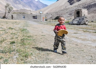 Khorog, Tajikistan - circa September 2011: Small boy holds large cake and looks to hotocamera in Khorog, Tajikistan. Documentary editorial.