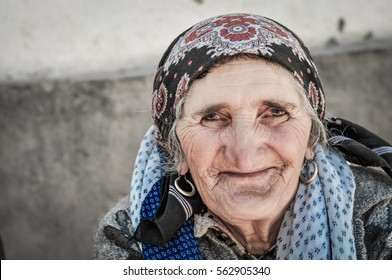 Khorog, Tajikistan - circa September 2011: Older woman with headcloth and earrings smiles nicely to photocamera in Khorog, Tajikistan. Documentary editorial.