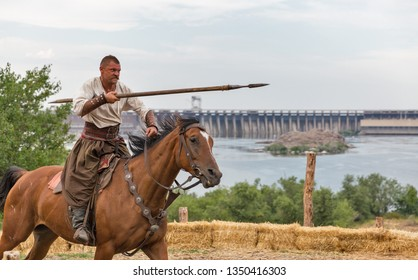 KHORTYTSIA, UKRAINE - JULY 03, 2018: Ukrainian Cossack horseman galloping with spear in Zaporozhian Sich. It was inhabited by Cossacks who lived beyond the rapids of Dnieper River in 15-18th century.