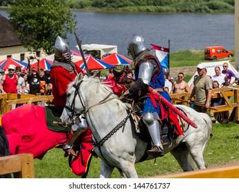 KHOTYN, UKRAINE - 10 MAY 2013: Two knights fighting on horseback with swords. Medieval Khotyn Festival. Khotyn, Ukraine, 10 May 2013
