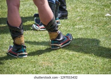 KHOVD, MONGOLIA - JULY 06, 2017:  Mongolian wrestlers wrestling in nature. Traditional Mongolian wrestler shoes.