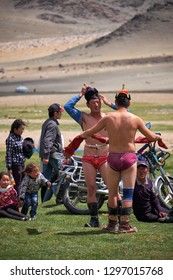 KHOVD, MONGOLIA - JULY 06, 2017:  Mongolian nomad camp. Mongolian wrestlers wrestling in nature. Spectators in national clothes watch the competition.