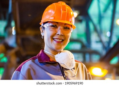 Khromtau, Aktobe region, Kazakhstan - May 06 2012: Gold ore mining and processing concentrating plant. Portrait of young Asian worker woman in orange hardhat. Posing and smiling.