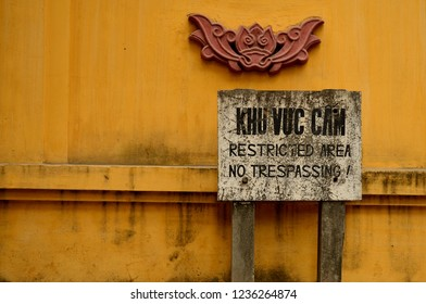 """""""Khu Vuc Cam"""" meaning restricted area no trespassing sign in front of a government building with a lotus on its yellow walls in Hanoi, Vietnam."""