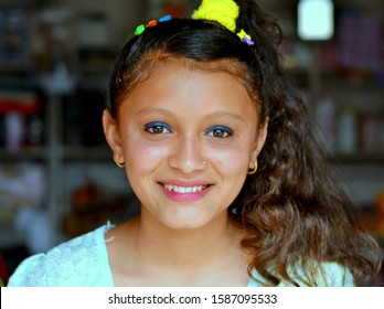 KHUDI, ANNAPURNA CIRCUIT / NEPAL - APRIL 10, 2016: Nepali Brahmin girl with blue eye makeup and beautiful long hair smiles for the camera, on April 10, 2016.