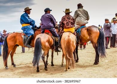 Khui Doloon Khudag, Mongolia - July 12, 2010: Horseback spectators at Nadaam (Mongolia's most important festival whose roots lie in Mongolian warrior traditions) horse race near capital Ulaanbaatar.