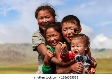 Khujirt, Övörkhangai, Mongolia - 07 19 15: Relaxed and informal landscape portrait of four happy Mongolian children with the focus on the youngest child who are nomad sisters and brothers