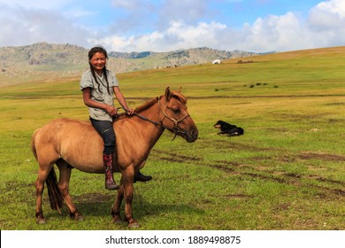 Khujirt, Ovorkhangai, Mongolia - 07 19 15: Smiling Mongolian girl with pigtails rides a bareback horse in the beautiful Mongolian landscape