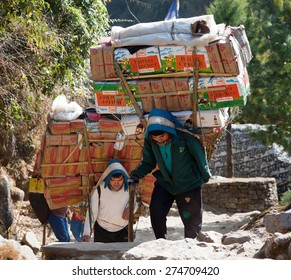 KHUMBU, NEPAL, 1st DECEMBER 2014 - Sherpa porters with goods going from Lukla to Namche Bazar, way to Everest base camp, Khumbu valley, Sagarmatha national park, Nepal