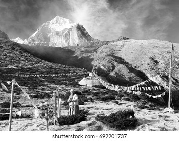 KHUMBU VALLEY, NEPAL - 8th NOVEMBER 2014 - Buddhist monk, stupa and prayer flags near Pangboche monastery and Tabuche peak, life in Khumbu valley on the way to Everest base camp, black and white view