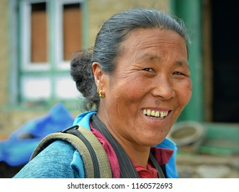 KHUMJUNG, NEPAL - MAY 4, 2017: Happy elderly Nepali woman of Tibetan origin smiles for the camera in front of her village home, on May 4, 2017.