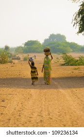 Khuri, India - November 26, 2009: A rural village Indian mother and daughter fetching water at the community well balancing jugs in the dry desert climate on a stretch of dirt unpaved road