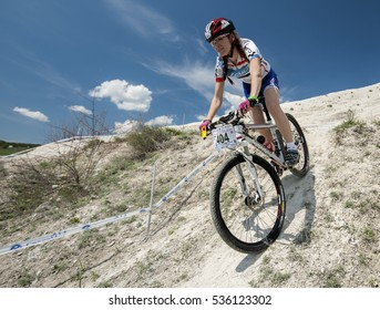 KHVALYNSK - MAY 7, 2016: Female cyclist descends from the slope at XCE eliminator track public open championship 'Match of Russian cities' on May 7, 2016 in Khvalynsk, Saratov region, Russia.