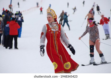 Khvalynsk, Russia - March 20, 2021: Winter mountain ski festival, people riding on snowboard or skiing in costumes and swimsuits; happy woman in costume